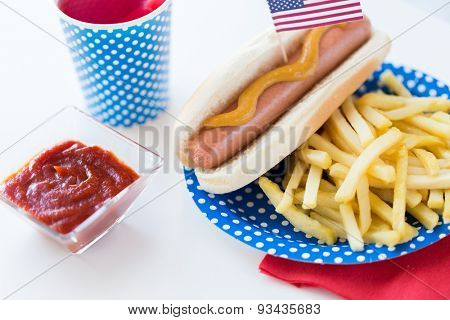 national holidays, celebration, food and patriotism concept - close up of hot dog with american flag decoration, french fries and drink in disposable paper cup on 4th july at party on independence day