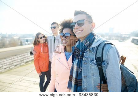 tourism, travel, people and leisure concept - group of happy teenage friends in sunglasses hugging on city street