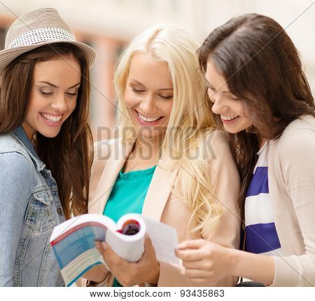 holidays and tourism concept - beautiful girls with city guide book