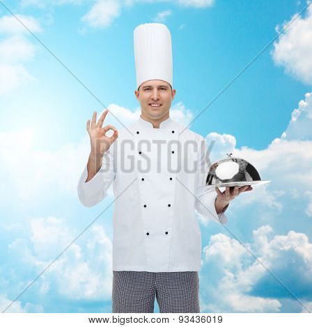 cooking, profession, gesture and people concept - happy male chef cook holding cloche and showing ok sign over blue sky with clouds background