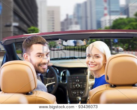 drive, auto transport and people concept - close up of happy couple driving in cabriolet car from back over city street background