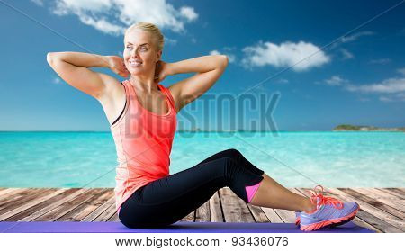 fitness, sport, exercising and people concept - smiling woman doing sit-up on mat over sea and wooden berth at resort background