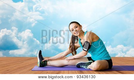fitness, sport, training and people concept - smiling woman with smartphone and earphones listening to music and stretching leg on exercise mat over wooden floor and sky with white clouds background