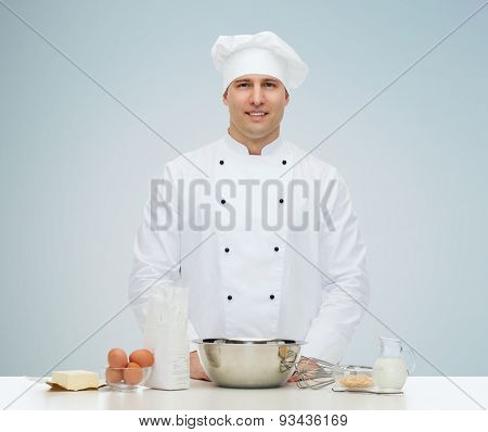cooking, profession, haute cuisine, food and people concept - happy male chef cook baking over gray background