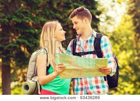 travel, vacation, tourism and friendship concept - smiling couple with map and backpacks looking at each other in forest