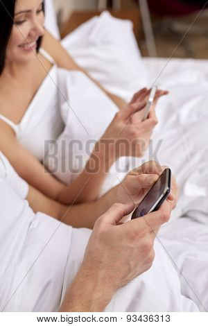 people, bedtime, technology and relations concept - close up of smiling couple in bed with smartphones texting message