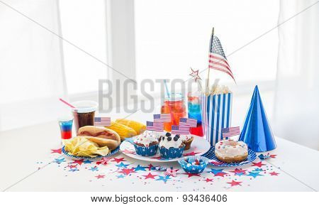 national holidays, celebration, food and patriotism concept - close up of hot dog with american flag decoration, potato chips and drinks on 4th july at home party on independence day