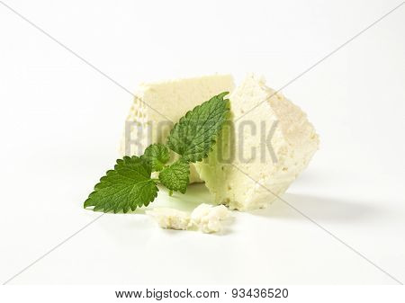 slices of fresh curd cheese and mint on white background