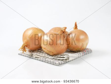 four raw onions on checkered dishtowel