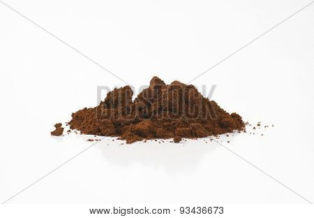 handful of freshly ground coffee on white background