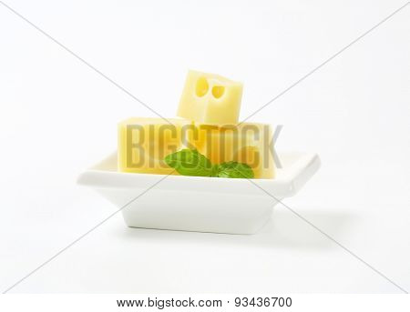 cubes of fresh emmental cheese in white bowl