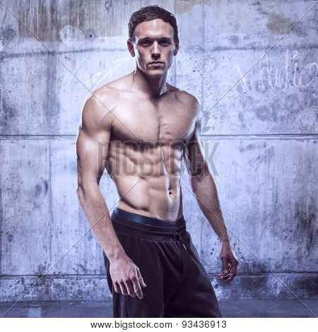 fitness male model in old garage rusted walls
