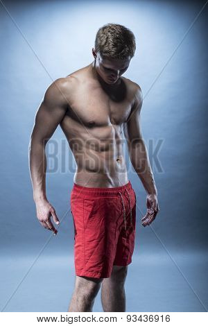 blonde Male fitness model wearing red shorts on blue