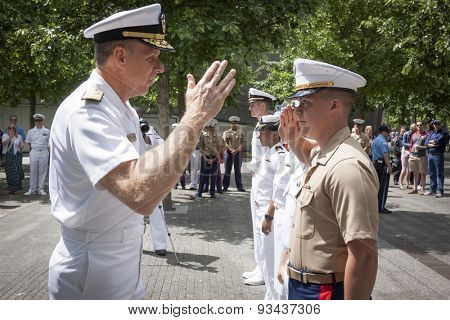 NEW YORK - MAY 22 2015: A US Marine renders a salute to Admiral Phil Davidson, Commander, US Fleet Forces Command, during the promotion ceremony at the National September 11 Memorial site.