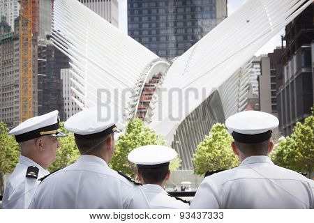 NEW YORK - MAY 22 2015: US Navy officers by the reflecting pool at the National September 11 Memorial site, with the white spokes of the World Trade Center Transit Hub in the background.