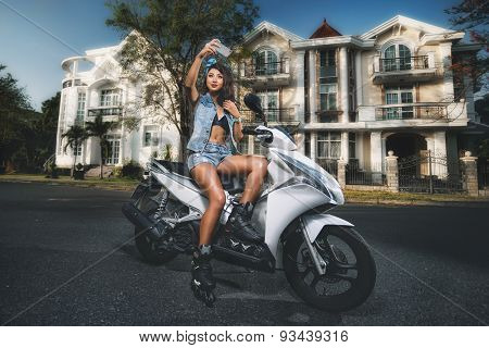 Attractive girl taking selfie while sitting on her scooter