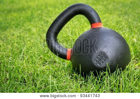 heavy iron competition kettlebell (62lb - 28 kg) on green grass in backyard - outdoor fitness concept