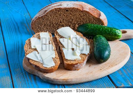 Freshly Baked Bread, Cucumber And Butter All For Sandwich In Rural Or Rustic Kitchen On Vintage Wood