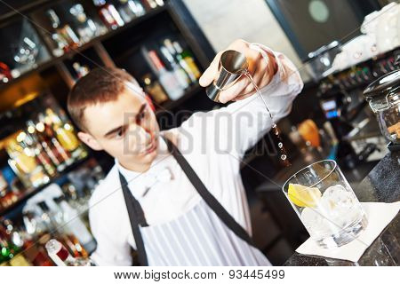young barman worker at bartender desk in restaurant bar preparing coctail