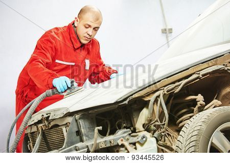 auto mechanic worker sanding polishing car at automobile repair and renew service station shop by sandpaper