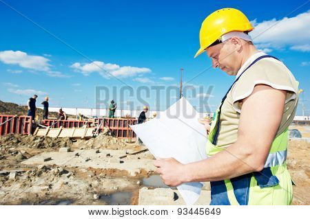 construction builder worker with blueprint project at building site