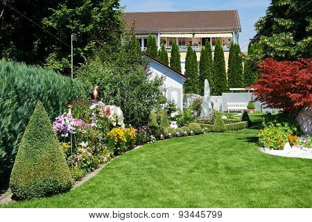 landscape design. Garden with green grass and flowers near cottage