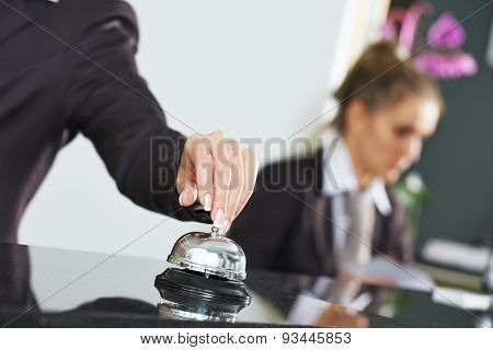 female receptionist worker ringing at hotel counter bell