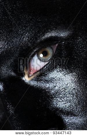 Closeup of woman eye with creative makeup with black and golden colors