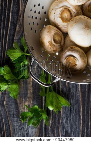 Fresh white champignons in a colander on dark wooden table