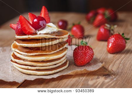 Homemade pancakes delicious breakfast or lunch dessert with strawberry, honey and butter on rustic k