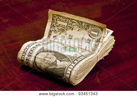Folded Worn Dollar Bills On Counter