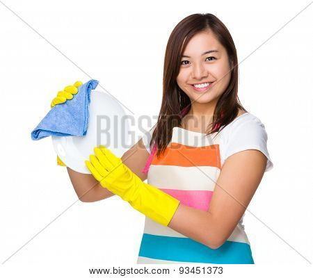 Young housewife washing dishes with rag