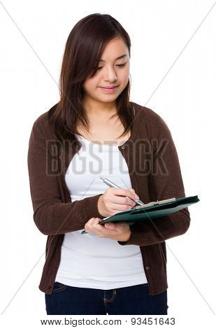 Asian woman write on clipboard
