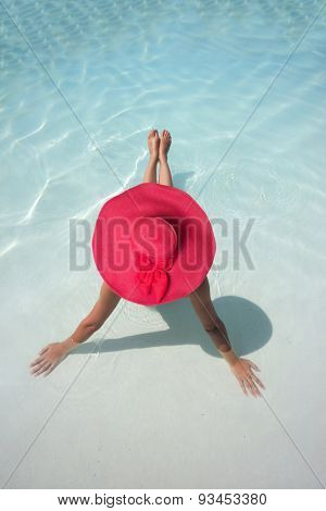 Woman with hat relaxing in a blue pool