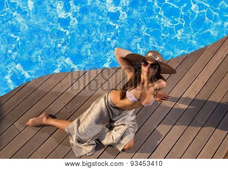 Woman wearing a straw hat by the swimming pool