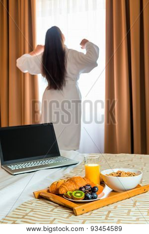 Woman In A Bathrobe Stretches In The Morning Near The Window