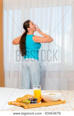 Woman In Pajamas Yawning Standing By The Window