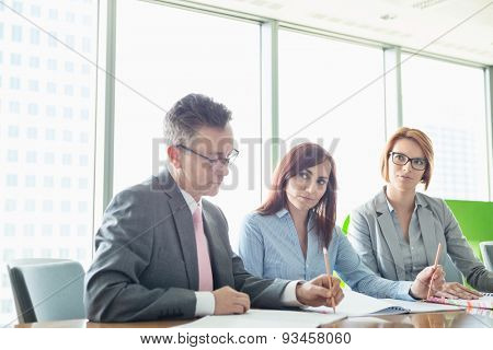 Business people writing on books at conference table