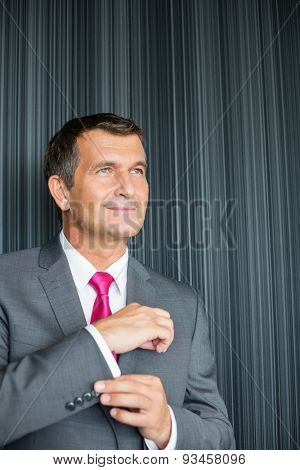 Mature businessman buttoning sleeve against wall