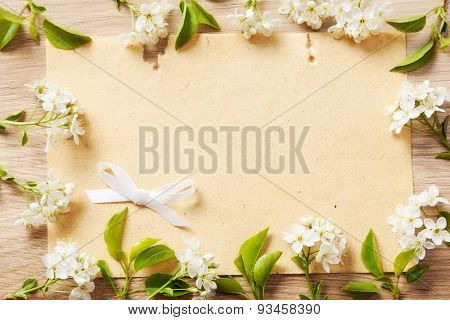 sheet of paper with a frame of flowering branches of cherry and white bow on a wooden background