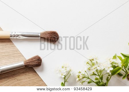 blank white sheet with a brush and a sprig of cherry blossoms. background