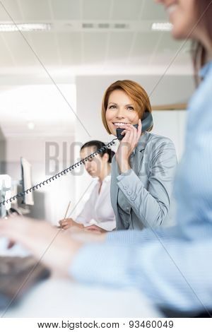 Smiling young businesswoman using landline phone in office