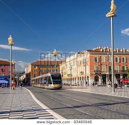 NICE, FRANCE - OCTOBER 2, 2014: Nice tramway entering Place Massena, the main pedestrian square of the city. Artworks surround the line including sculptures of figures by Jaume Plensa on top of pylons