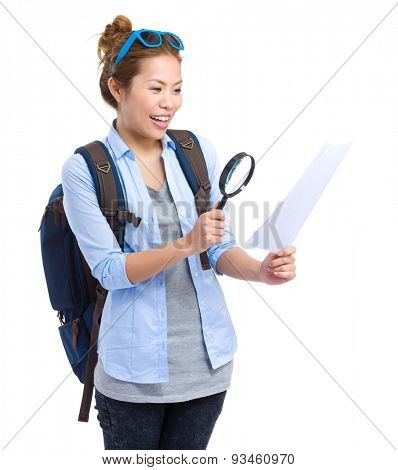 Woman using magnifying glass for the map