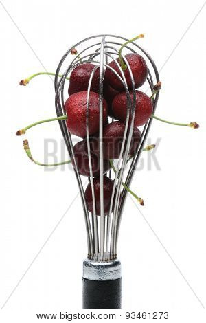 A metal whisk filled with fresh ripe cherries. Vertical format on white.