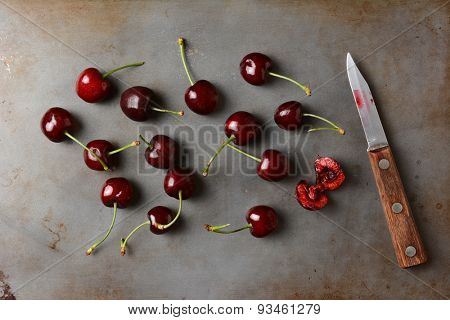 Fresh ripe cherries on a baking sheet with knife. High angle shot with one cherry sliced into exposing its flesh.