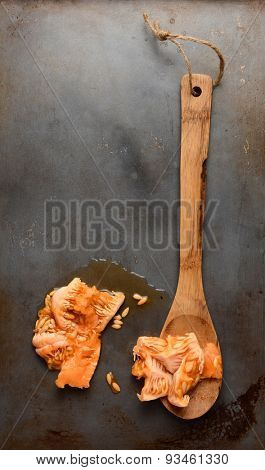 High angle shot of a wood spoon and the seeds and pulp scooped from a cantaloupe. Overhead view in vertical format with copy space.