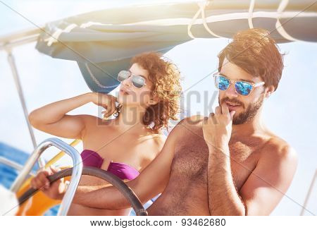 Happy lover driving sailboat, handsome captain with his cute girlfriend at the wheel of water transport, active lifestyle, interesting summer vacation