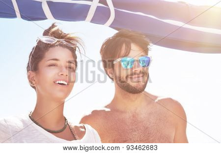 Portrait of handsome guy and beautiful woman having fun on sailboat in sunny day, best friends spending summer vacation in the sea cruise