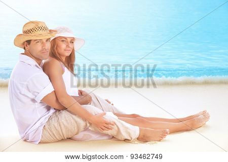 Happy lovers on the beach, beautiful young couple sitting on sandy coast and hugging, enjoying each other and romantic honeymoon vacation